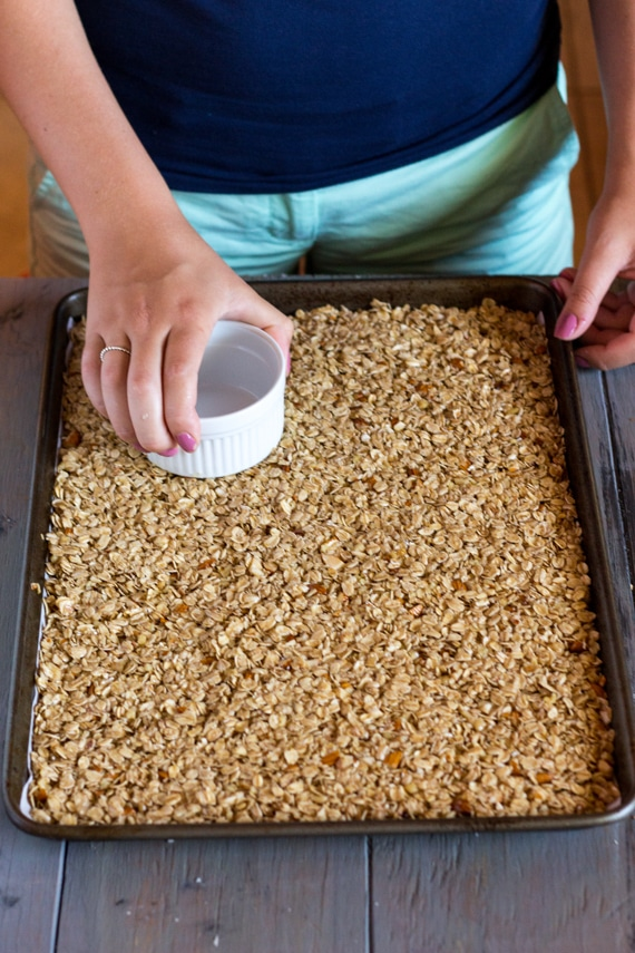 A woman is using a ramekin to distribute Crunchy Homemade Granola evenly throughout the pan