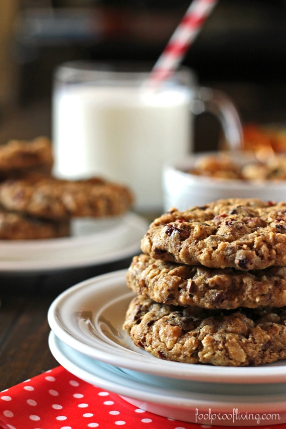 A few chunky oatmeal cookies are placed on top of each other with a glass of milk