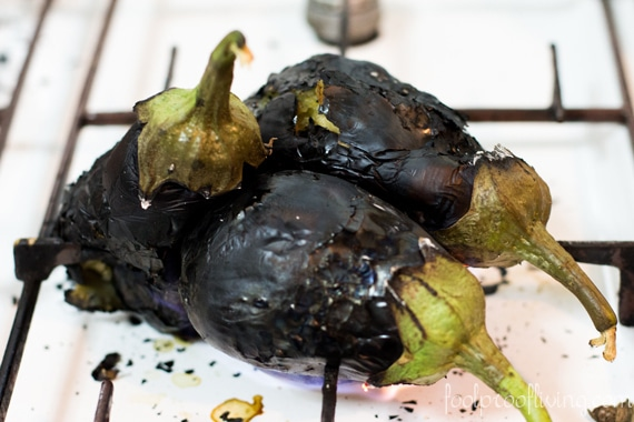 Eggplants are being roasted on fire on the stove