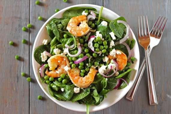 Shrimp and Spinach Salad served in a bowl and topped off with peas