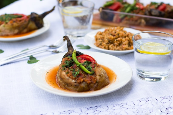 Eggplant ground beef Turkish recipe is placed in a white plate served with bulgur.