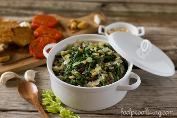 A bowl of spanish spinach recipe uis served with bread on the side.