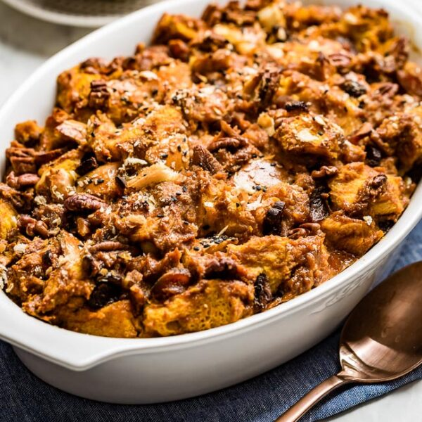 Pumpkin Bread Pudding in a casserole dish with a spoon on the side