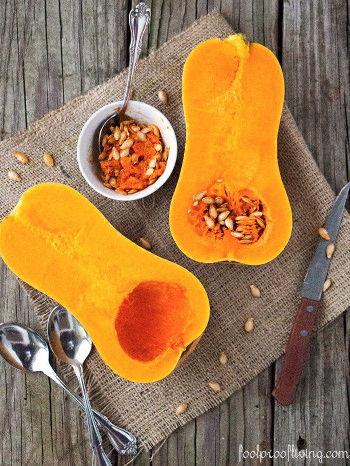 Whole Squash sliced in half with a cup of pulp and seeds on a knife, spoons and additional seeds on napkins