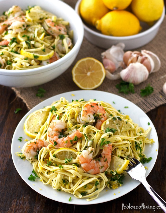 A bowl  and a plate Linguine with Shrimp Scampi with a bowl of lemons, sliced lemon and garlic