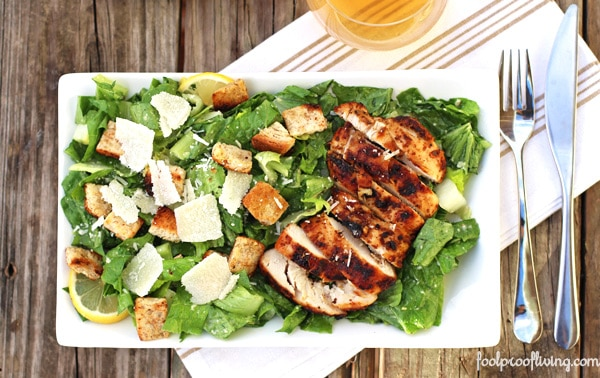 A square plate of Classic Caesar Salad on a napkin with tableware.