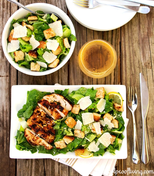 Overhead shot of a bowl and a plate ofClassic Caesar Salad with a glass of wine and tableware on a table