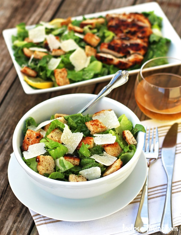 A bowl and plate of Classic Caesar Salad with a glass of wine with tableware and napkin