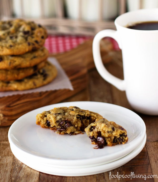 a half eaten chocolate chip cookie with coffee on the side