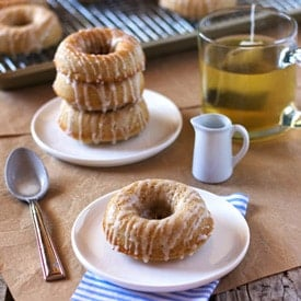 ina garten baked cinnamon doughnuts placed on a plate with tea in the background