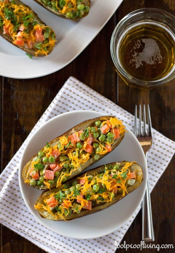 2 Loaded Twice-Baked Potato Skins on a plate 2 more baked potato skins on another plate with a fork on a napkin and a glass of beer on the side