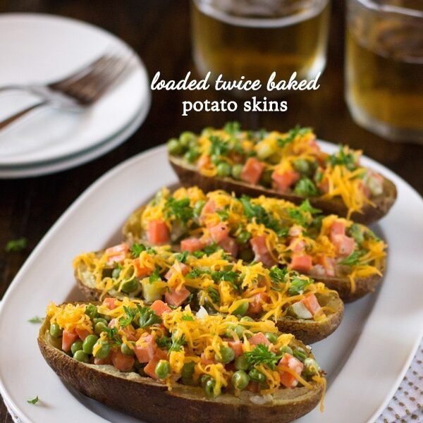 4 Loaded Twice-Baked Potato Skins on a plate with a glass of beer on the side