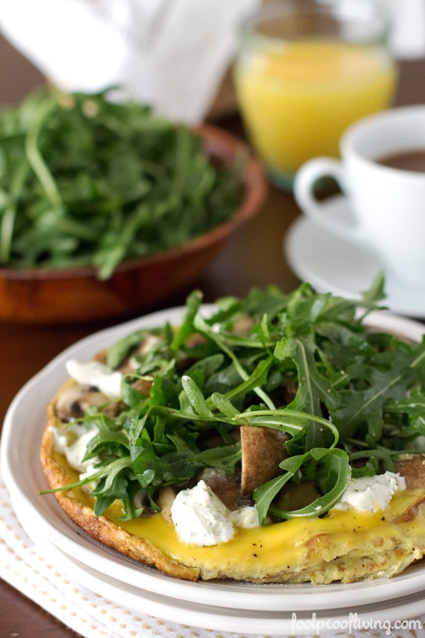 Close up view of West Egg's Portobello Frittata on a plate with a cup of coffee, glass of orange juice and a plate of spinach in the background