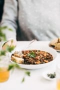 A bowl of French Lentil Soup is photographed in front of a woman as she is getting ready to eat it.
