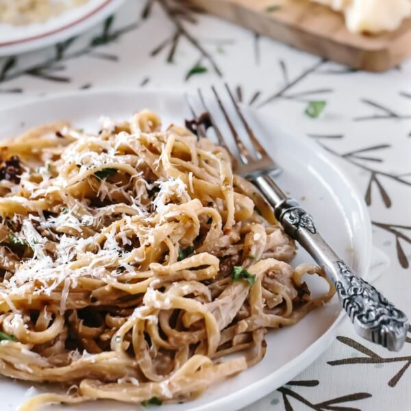 Linguine with Walnut Bachamel Sauce and Sun-Dried Tomatoes on a plate with a fork on the side