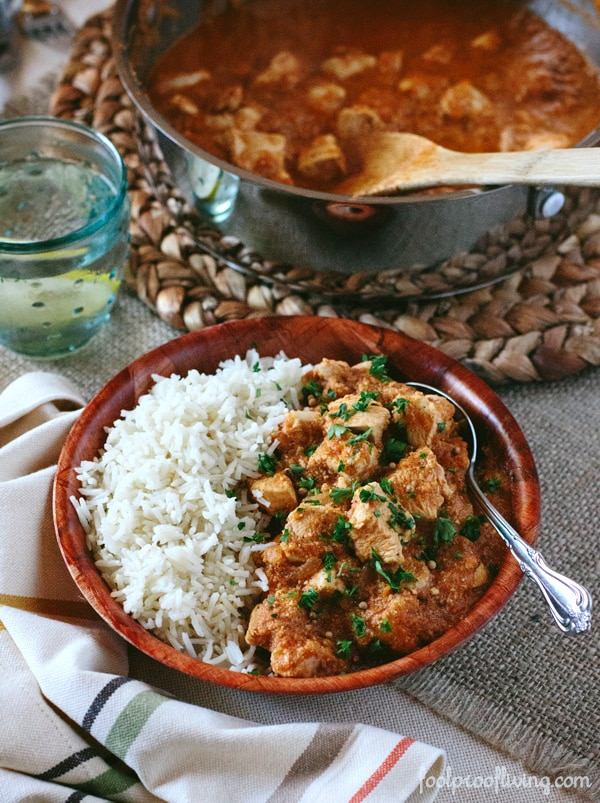Chicken Curry with Gentle Spices in a bowl with rice with a glass and pot of chicken curry and a spoon