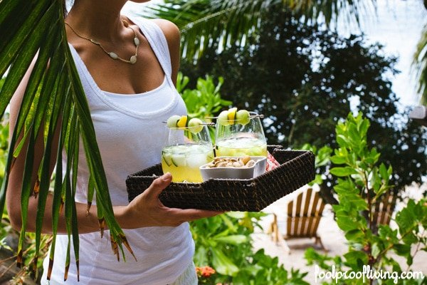 Person carrying a tray of Cocktails surrounded leaves and a chair in the background
