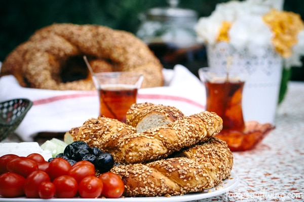 A plate full of Simit, tomatoes, olives along with Turkish tea are photographed from the front view.