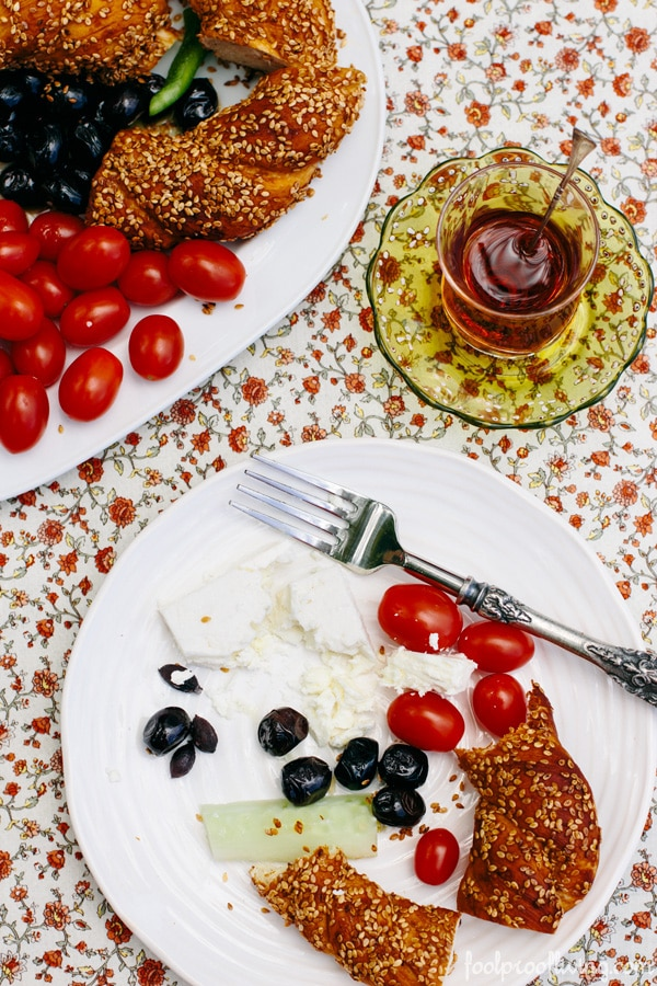 A plate full of half eaten Simit along with olives, tomatoes, Turkish Tea and feta cheese are photographed from the top view.