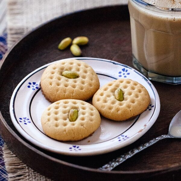 Three Tahini Cookies with Pistachios with a glass of chocolate milk and pistachios on the side
