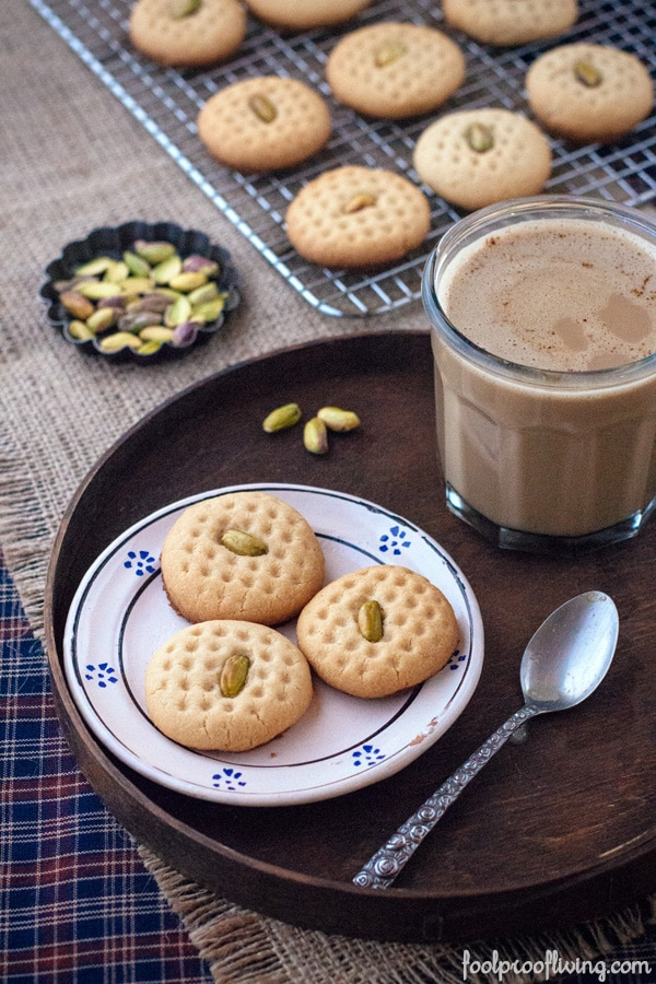 Tahini Cookies with Pistachios on a plate with more on a cooling rack with pistachios and a glass of chocolate milk on the side
