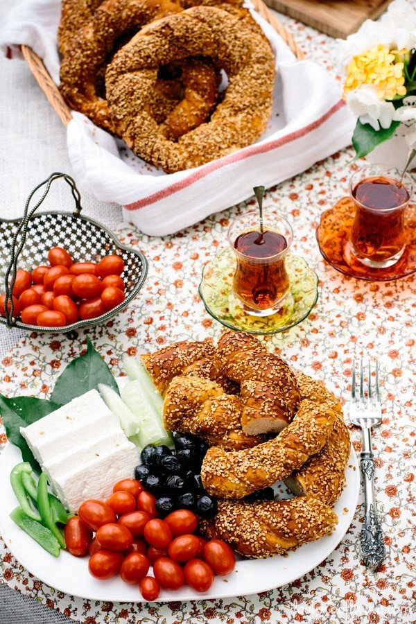 A plate full of Turkish Simit, feta cheese, olives, and tomatoes are photographed from the front view.