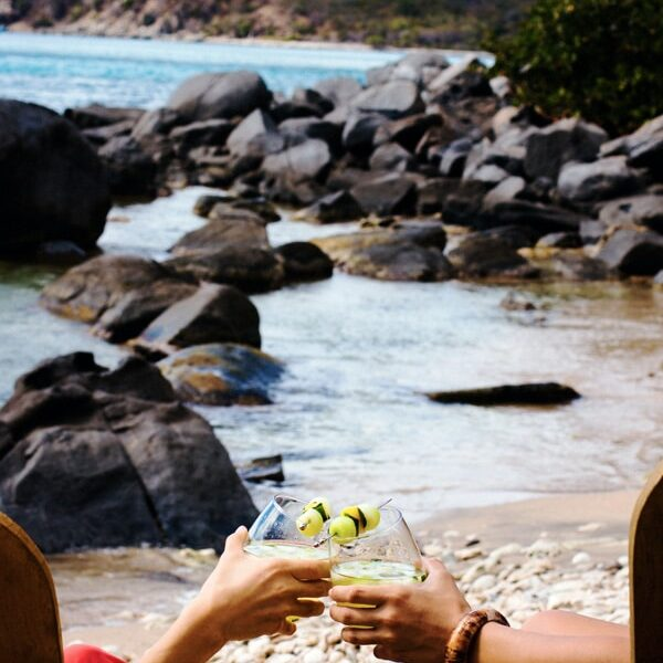 Two people sitting on a beach holding two Women on the Rock A Caribbean Cocktail