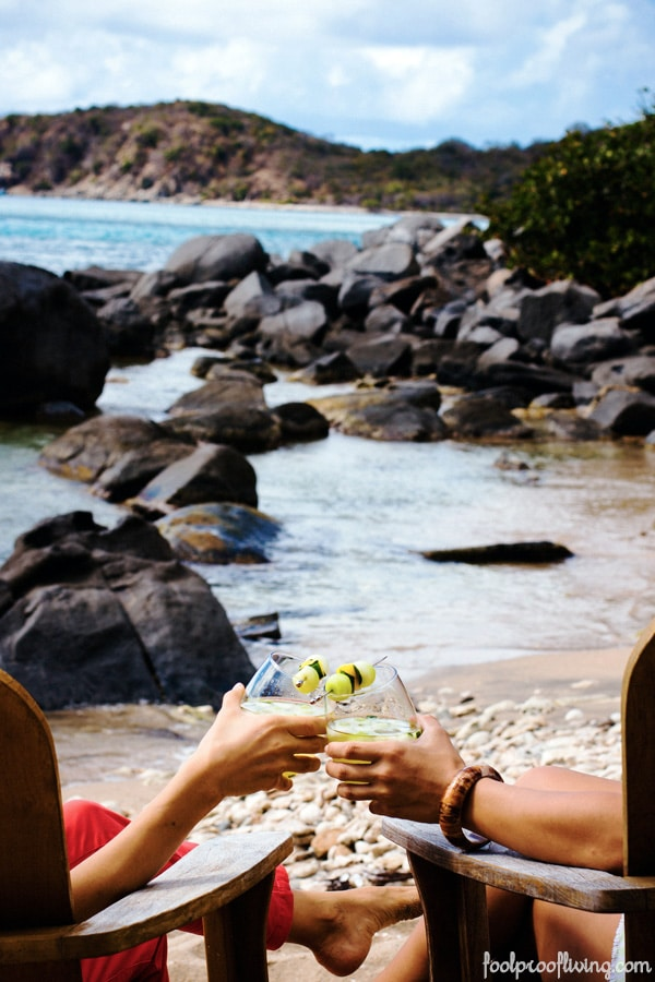 Two people sitting on a beach holding Women on the Rock {A Caribbean Cocktail}