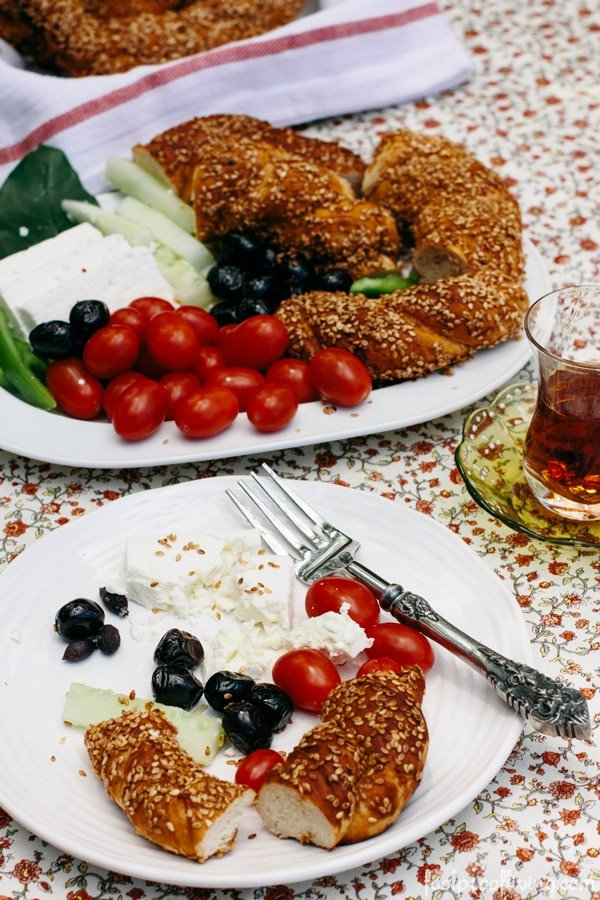 A plate full of half eaten Simit is photographed with feta cheese, olives, and tomatoes.