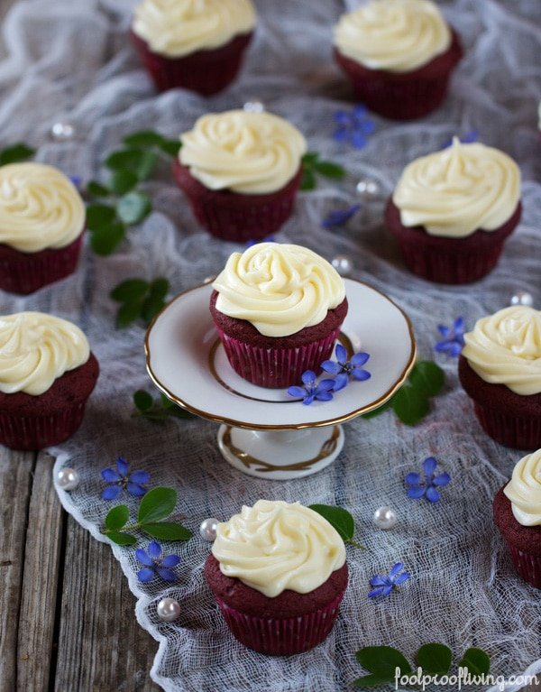 The Best Red Velvet Cupcakes Recipe- several cupcakes on a wooden board with pearl and flowers