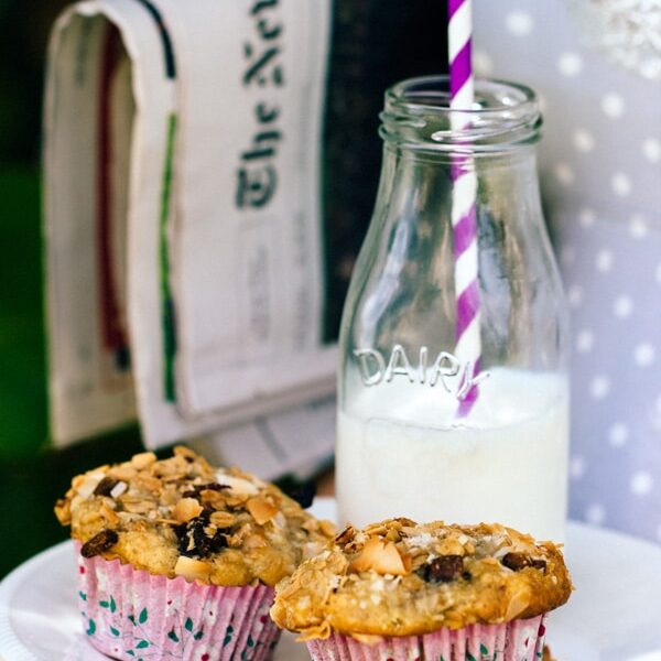 Two Granola Top Banana and Coconut Muffins with a jar of milk with a straw and newspaper