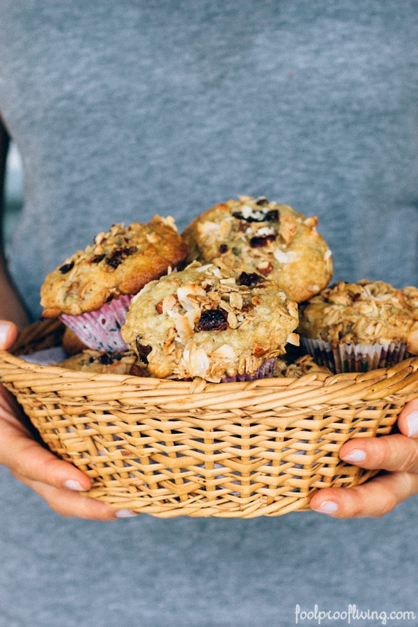 Person holding a basket of Granola Top Banana and Coconut Muffins