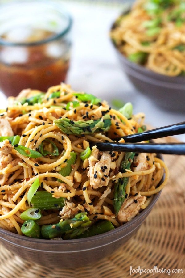 Close up view of Chicken Asparagus Noodles in a bowl with chopsticks