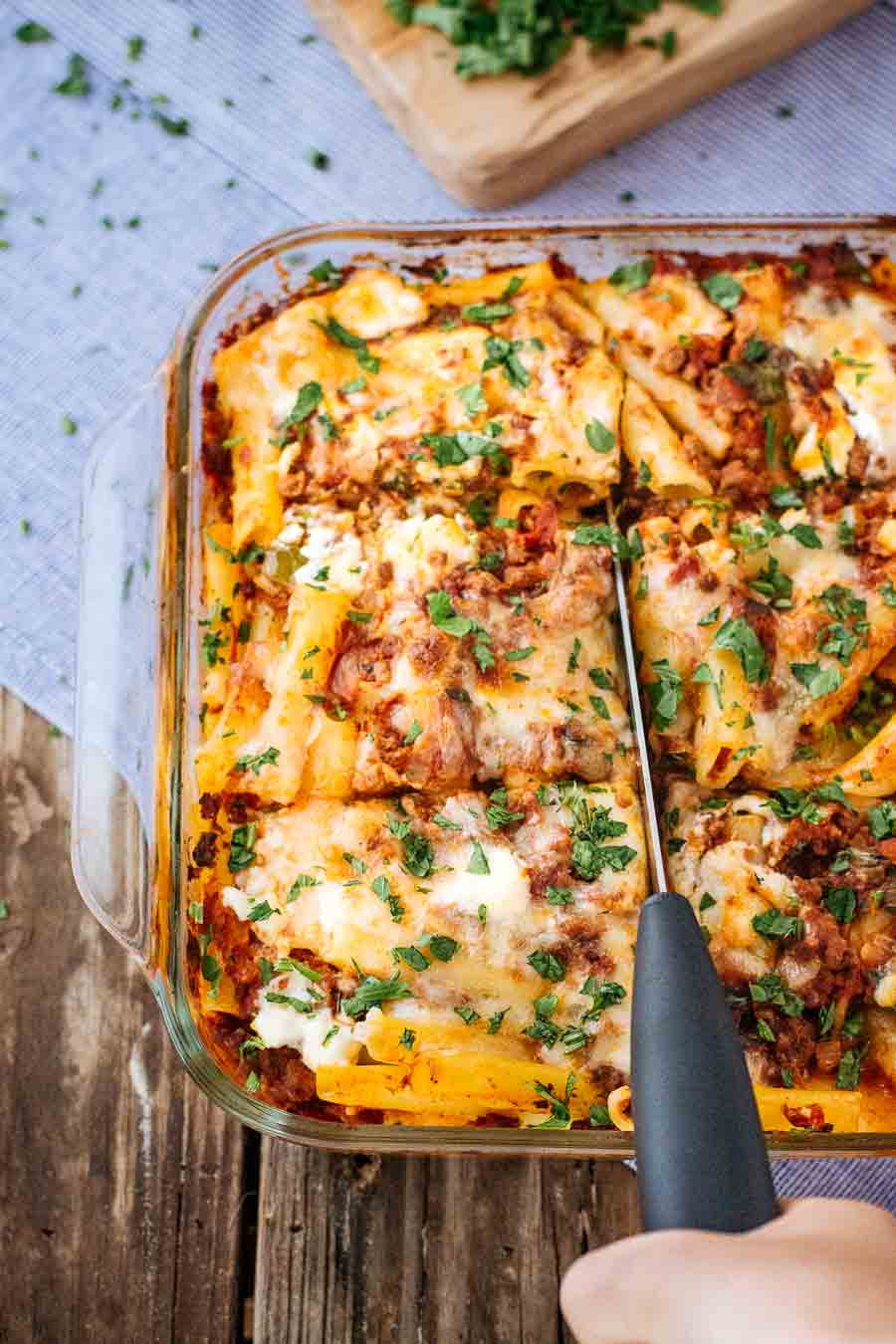 A woman is photographed from the front view as she is cutting into a freshly baked pasta bake