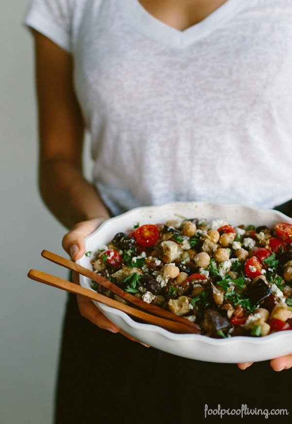 Woman holding a bowl of Mediterranean Chickpea, Farro, and Za'atar Salad
