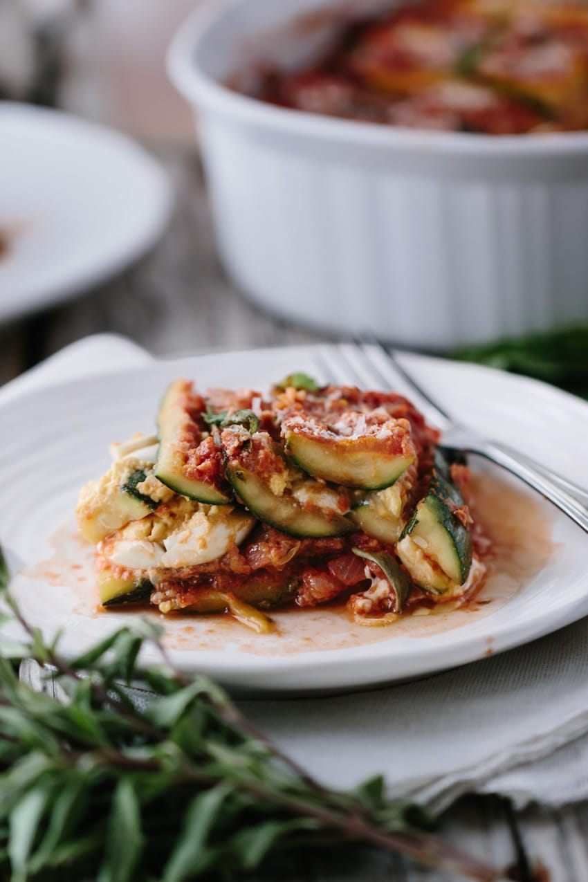 A serving of zucchini lasagna on a plate with a fork on the side.