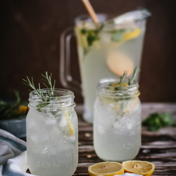 Mint and Rosemary Lemonade with Vanilla in mason jars garnished with rosemary sprigs
