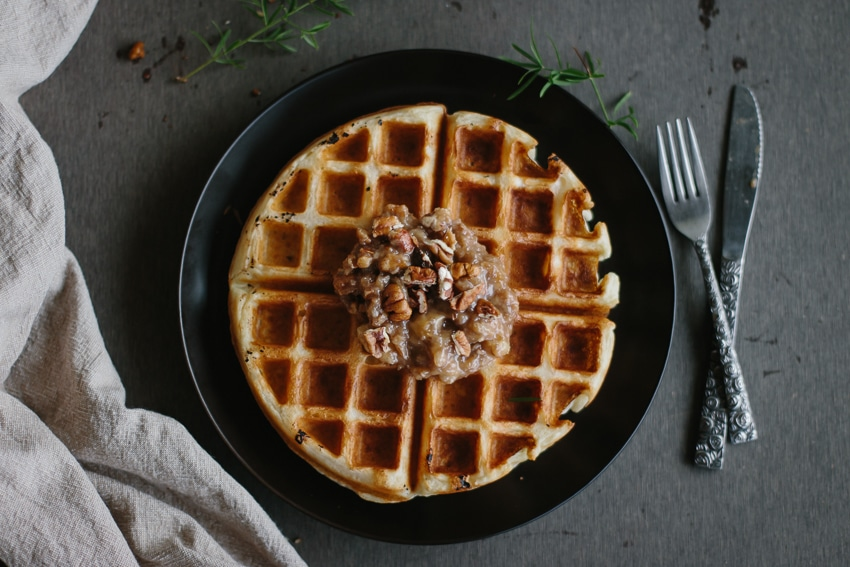 Overhead view of Overnight Yeasted Waffles with Banana-Rum Topping on a plate with flatware of the side