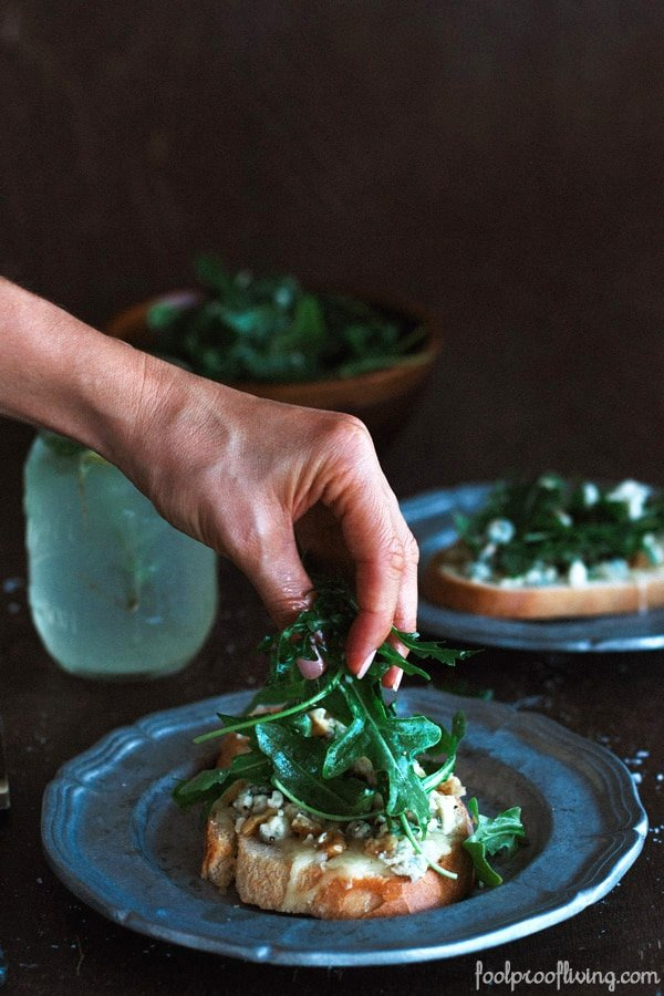 Person placing greens on top of Gorgonzola-Walnut Bruschetta with Truffle Oil