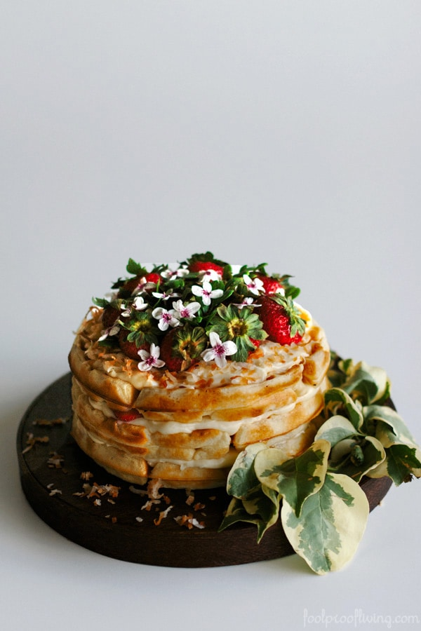 Strawberry Waffle Cake with Coconut Frosting on round platter with decorative leaves
