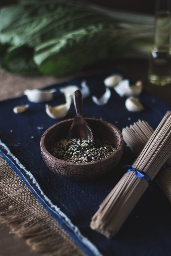 Ingredients for Soba Noodles with Bok Choy on a blue napkin and garlic bulbs in the background