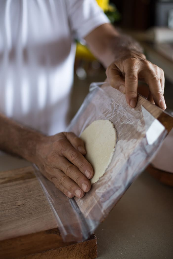 A man is showing how to flatten a corn tortilla to show how to make Corn Tortilla Recipe for beginners
