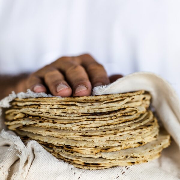 A man is holding a few Homemade Corn Tortillas in his hands