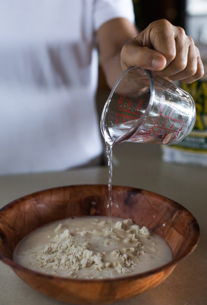 A man is pouring water into masa harina to show How to make Homemade Corn Tortillas with step by step photos