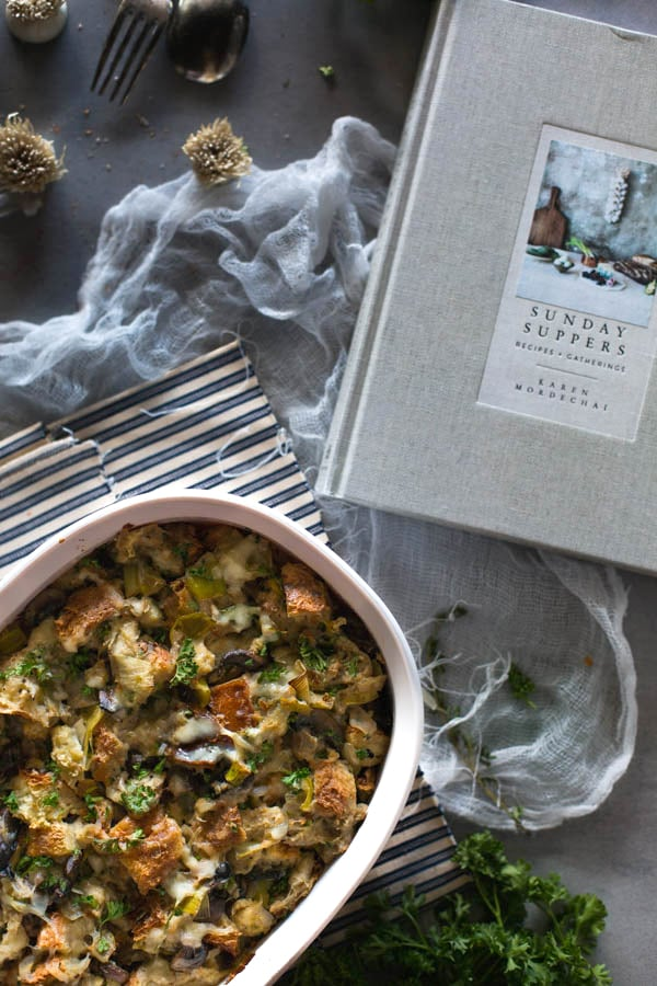 Overhead view of Brioche Stuffing in a casserole dish on a cloth napkin with a book on the side