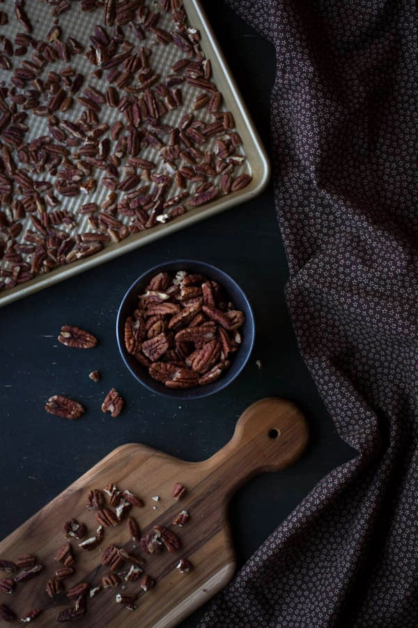 Chopped pecans on a cutting board, chopped pecans in a bowl and chopped pecans on a baking sheet with a decorative napkin on the side
