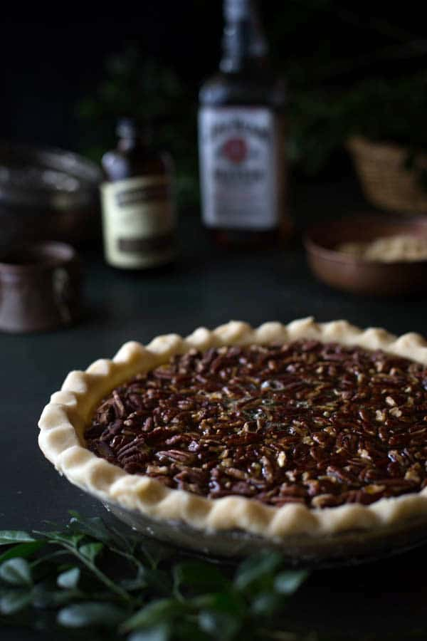 Frontal view on an Old-Fashioned Maple Pecan Pie with Bourbon Whipped Cream with a bottle bourbon faded in the background
