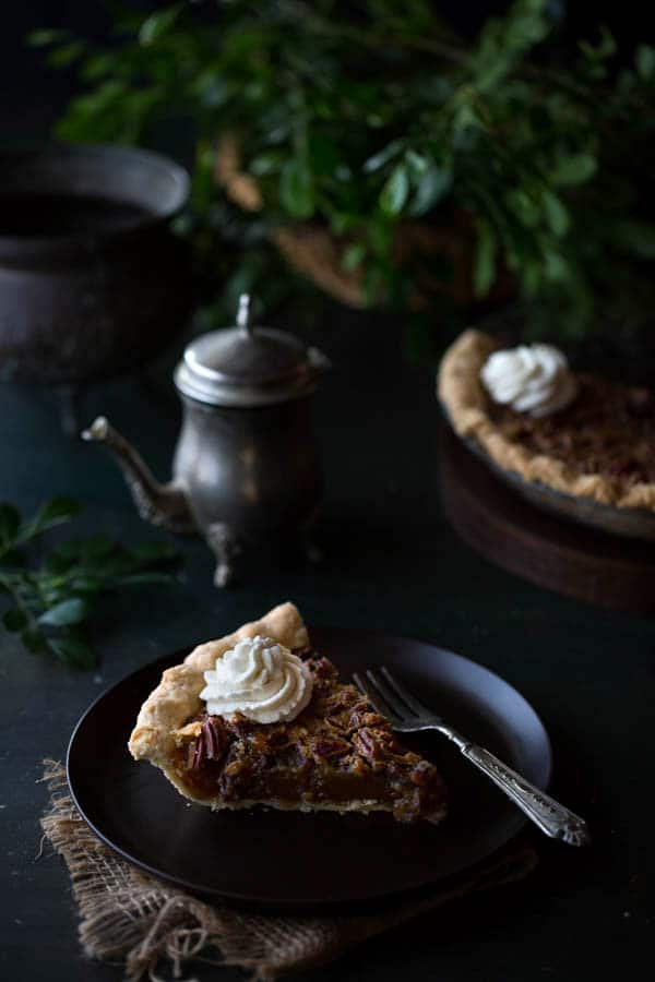 A single slice of Old-Fashioned Maple Pecan Pie with Bourbon Whipped Cream