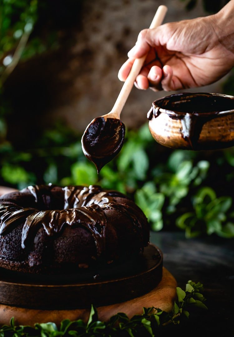 chocolate bundt cake recipe topped off with cocoa powder and the best chocolate glaze by a man with a wooden spoon