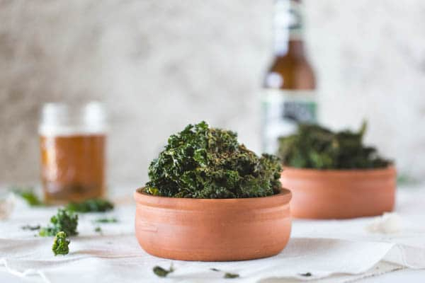 Side view of 2 bowls of Cheesy Oven-Roasted Kale Chips with a glass and bottle of beer in the background